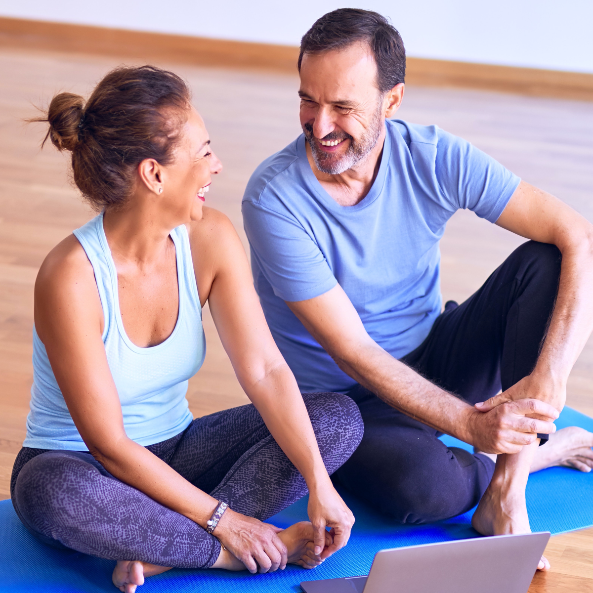 A woman and a man having a conversation on a yoga mat